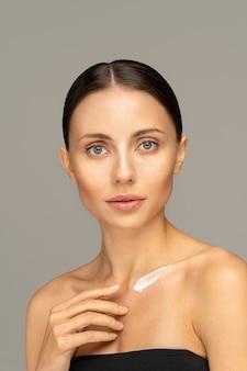 Zbliżenie na kobiety stosujące krem przeciwsłoneczny lub kosmetyczny balsam nawilżający na klatkę piersiową