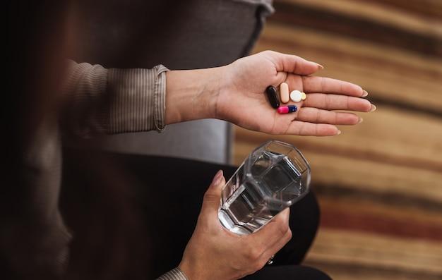 Zbliżenie na kobiety trzymającej różne tabletki, pigułki i szklankę wody.
