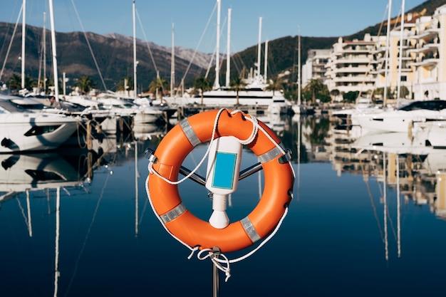 Zbliżenie na koło ratunkowe na stojaku na przystani z widokiem na góry i jachty na wodzie