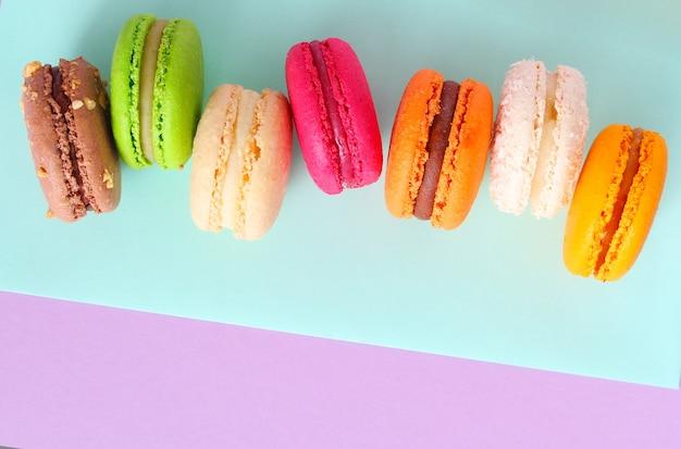 Zbliżenie na kolorowe francuskie makaroniki na tle mięty i fioletu