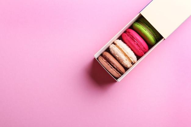 Zbliżenie na kolorowe francuskie makaroniki w pudełku na różowym tle