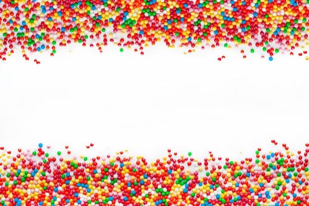Zbliżenie na kolorowe kulki cukru na białym tle