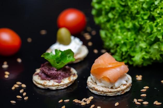 Zbliżenie na krakersy z pastą z oliwek, twarogiem i łososiem na nich na stole