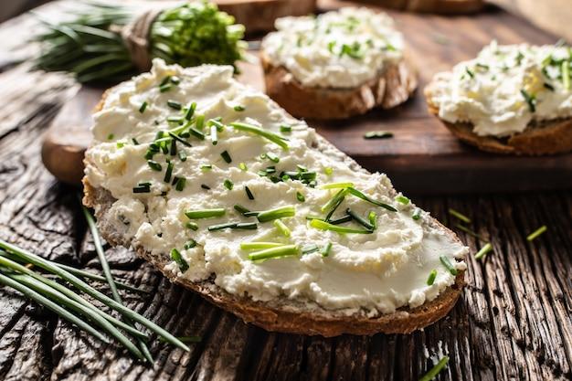 Zbliżenie na kromkę chleba z tradycyjną słowacką bryndzą z sera owczego ze świeżo pokrojonym szczypiorkiem na rustykalnym drewnie.