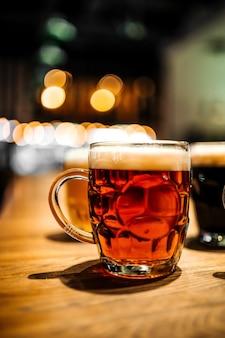 Zbliżenie na kubek ciemnego piwa rzemieślniczego w barze