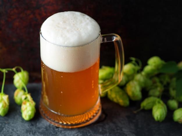 Zbliżenie na kubek niefiltrowanego piwa pszenicznego i zielonego chmielu