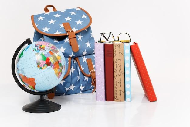 Zbliżenie na kulę ziemską, niebieski plecak z nadrukiem w gwiazdki i kolorowe podręczniki szkolne