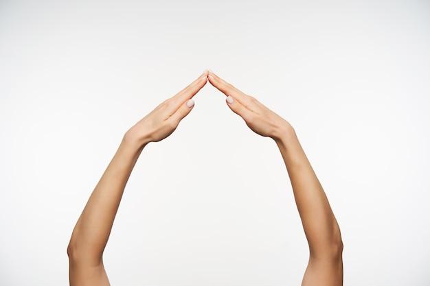 Zbliżenie na ładne ramiona imitujące dom ze złożonymi dłońmi