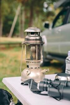 Zbliżenie na lampę naftową nad stołem kempingowym w naturze