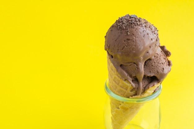 Zbliżenie na lody czekoladowe w rożku waflowym na żółtym tle. skopiuj miejsce.