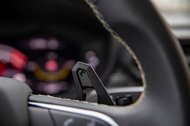 Zbliżenie na łopatki zmiany biegów na kierownicy w nowoczesnym samochodzie premium. ręczna zmiana biegów speedshift na kierownicy samochodu, detal wnętrza samochodu
