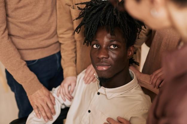 Zbliżenie na ludzi pocieszających młodego człowieka na wózku inwalidzkim podczas sesji terapeutycznej w grupie wsparcia, miejsce kopiowania