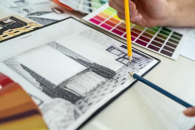 Zbliżenie na ludzkie ręce pokazujące próbnik kolorów i szkic wnętrza