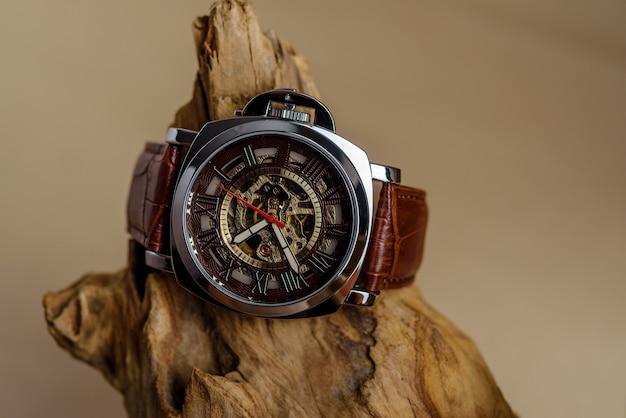 Zbliżenie na luksusowe zegarki na rękę umieszczone na drewnie w brązowej ścianie