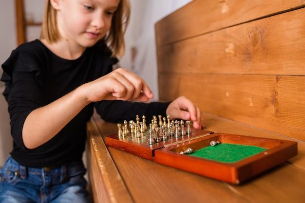 Zbliżenie na małą blondynkę siedzącą i grającą w szachy na szachownicy