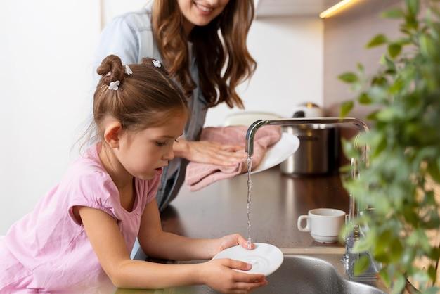 Zbliżenie na małą dziewczynkę pomagającą mamie z naczyniami