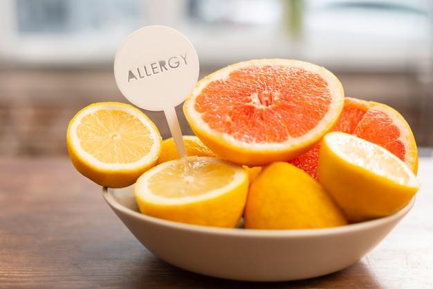 Zbliżenie na małą miskę z grejpfrutami i cytrynami z alergenami stojącymi na stole