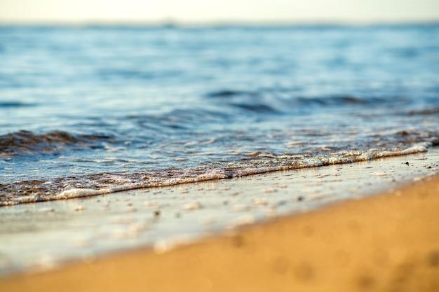 Zbliżenie na małe fale morza z czystą, błękitną wodą nad żółtą piaszczystą plażą w słoneczny letni brzeg.
