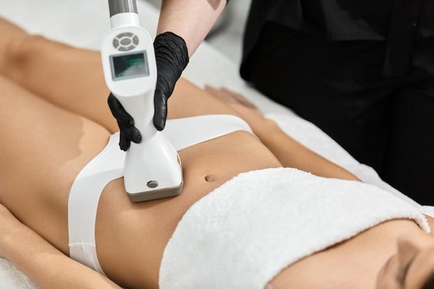 Zbliżenie na masaż donga masażysty kobiecego brzucha za pomocą urządzenia lpg