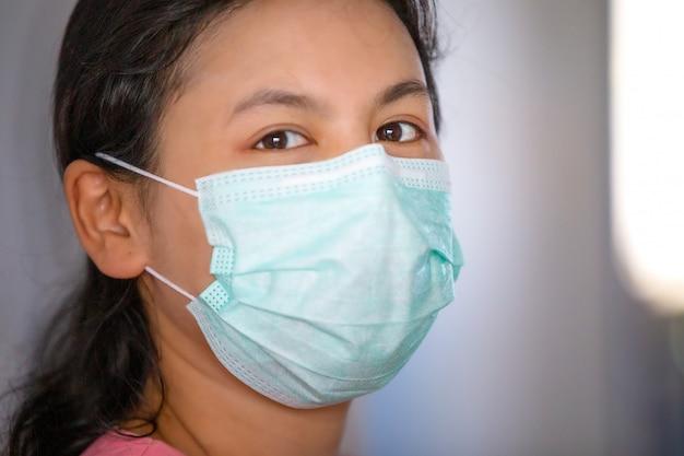 Zbliżenie na maska kobiety ochrony twarzy dla ochrony coronavirus przeciwko niewyraźne tło