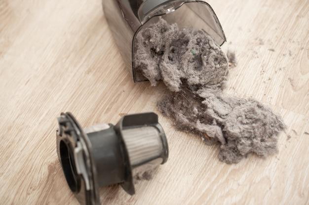 Zbliżenie na masowo zatkany, brudny filtr odkurzacza ręcznego, kurz i proszek na filtrze odkurzacza, gospodarstwo domowe