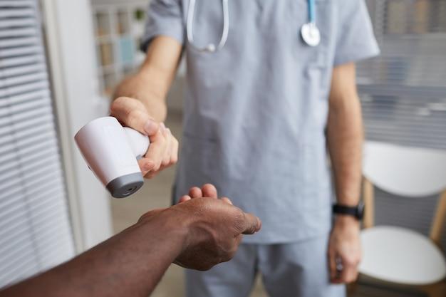 Zbliżenie na męski lekarz wskazujący termometr na podczerwień na ręce pacjenta podczas kontroli temperatury w szpitalu, miejsce kopiowania