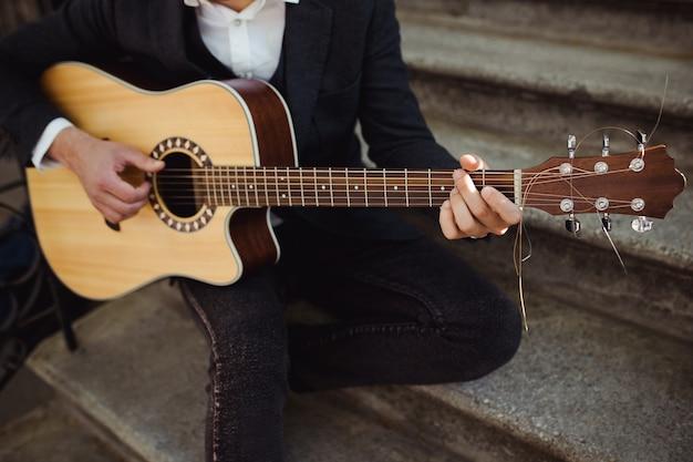 Zbliżenie na męskie dłonie gry na gitarze akustycznej na schodach