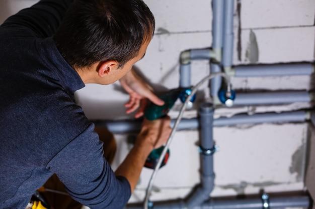 Zbliżenie na męskiego hydraulika naprawiającego rury w toalecie