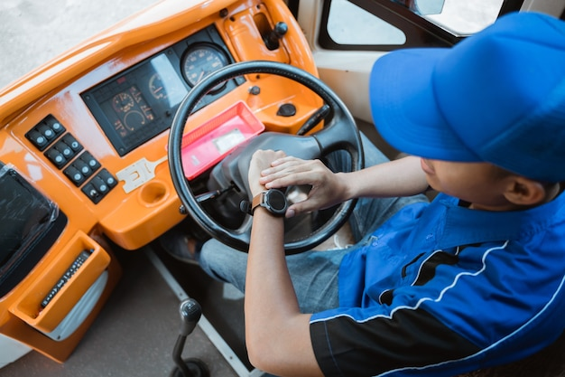 Zbliżenie na męskiego kierowcę w mundurze, patrzącego na zegarek, trzymającego kierownicę w autobusie