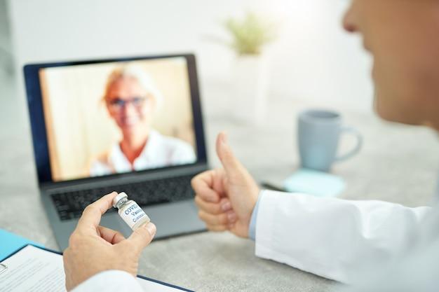 Zbliżenie na męskiego lekarza trzymającego butelkę szczepionki covid-19 i pokazującego gest zatwierdzenia podczas korzystania z laptopa do komunikacji online z kolegą