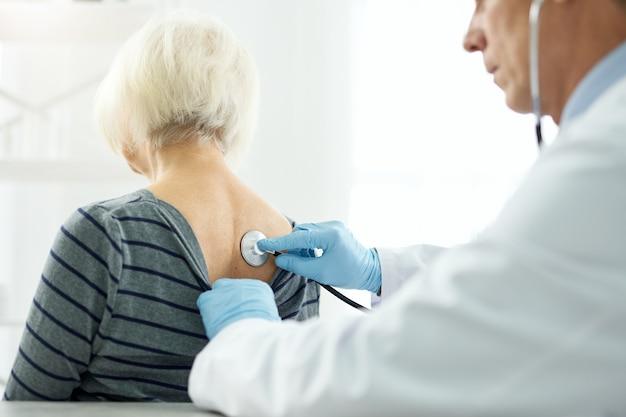 Zbliżenie na męskiego lekarza w sterylnych rękawiczkach, zakładającego stetoskop na plecy starej kobiety i sprawdzającego jej oddech