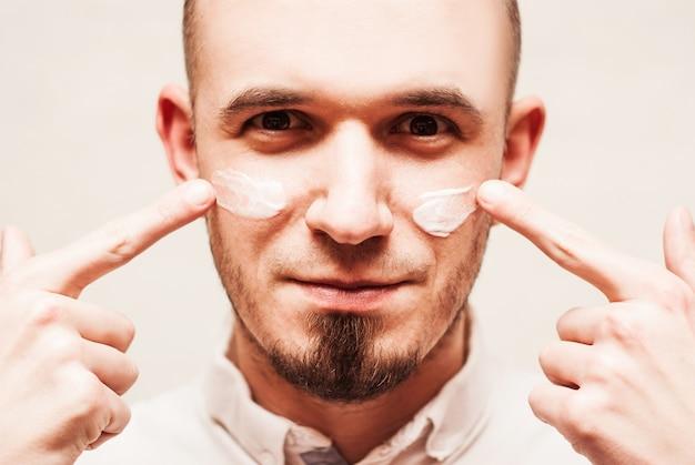 Zbliżenie na mężczyzna stosuje śmietankę na jego twarzy