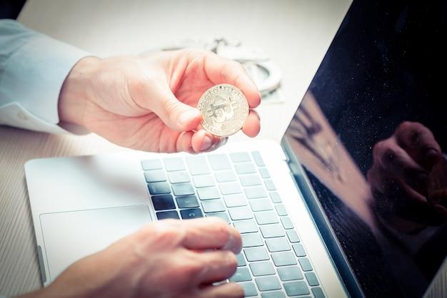 Zbliżenie na mężczyznę patrzącego uważnie na bitcoina w rękach na biurku