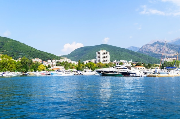 Zbliżenie na miasto budva z jachtu, w tle pasmo górskie z roślinnością. podróżuj wzdłuż wybrzeża czarnogóry.