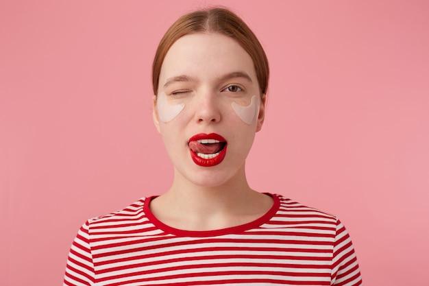 Zbliżenie na miłą, młodą rudowłosą damę z czerwonymi ustami i łatami pod oczami, ubrana w czerwoną koszulkę w paski, patrzy i mruga, pokazuje język, stoi.