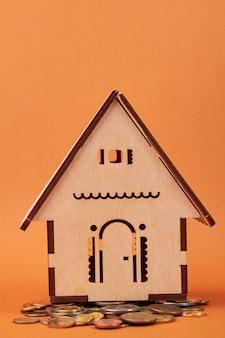 Zbliżenie na miniaturowy model domu i monety