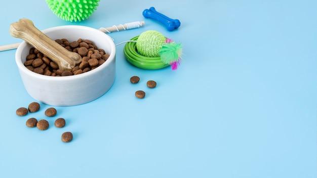 Zbliżenie na miskę z jedzeniem i zabawki do żucia w kształcie kości