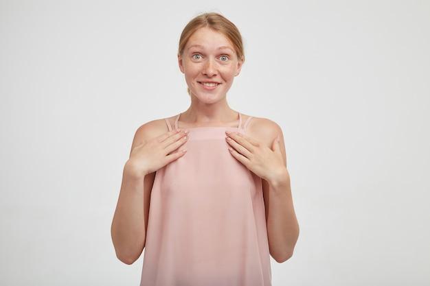 Zbliżenie na młodą atrakcyjną rudą kobietę z przypadkową fryzurą na białym tle