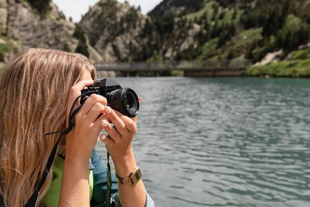 Zbliżenie na młodą kobietę robiącą zdjęcia aparatem