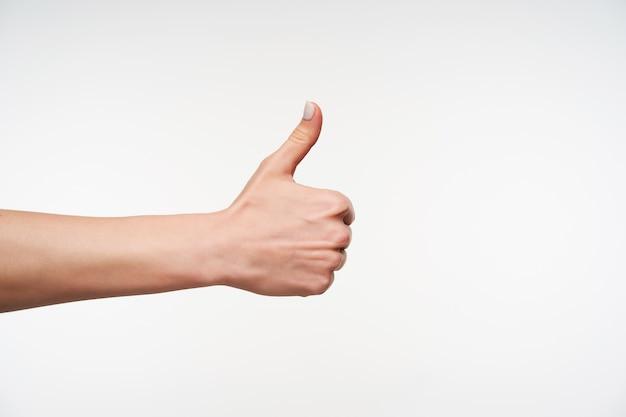 Zbliżenie na młodą kobietę z białym manicure, podnosząc rękę