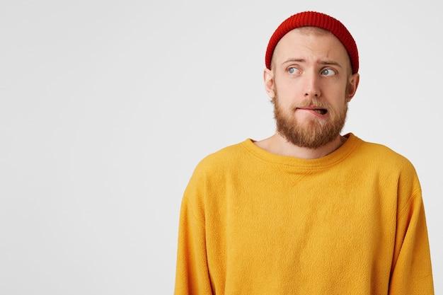 Zbliżenie na młodego faceta z czerwoną brodą, w czerwonym kapeluszu, tchórzliwy, ostrożnie wydrążający wargę