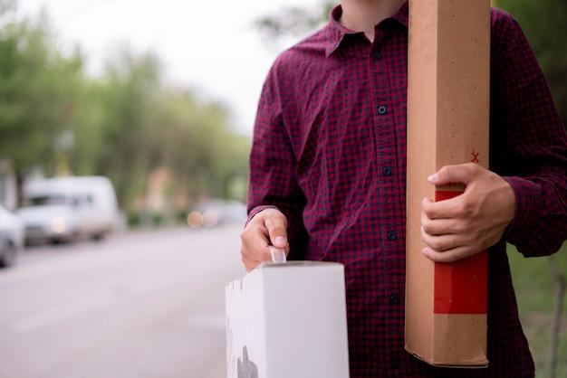 Zbliżenie na młodego kuriera czekającego na klienta klientów w mieście