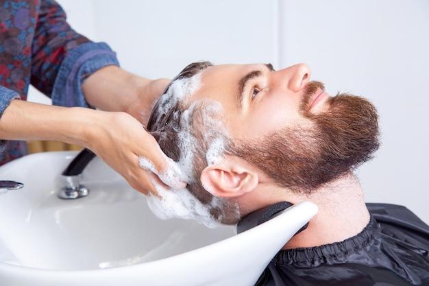 Zbliżenie na młodego mężczyznę rasy kaukaskiej, który myje włosy w salonie fryzjerskim