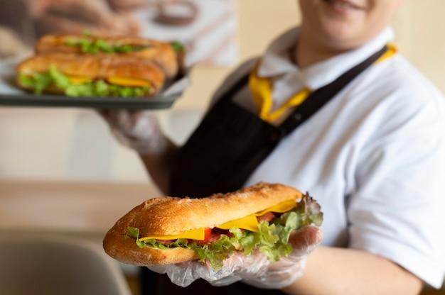 Zbliżenie na młodego szefa kuchni trzymającego kanapki