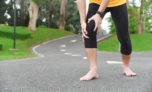 Zbliżenie na młody azjatycki sportowiec ma ból mięśni i stawów podczas ćwiczeń na świeżym powietrzu, podczas treningu lub biegania i koncepcji urazów sportowych