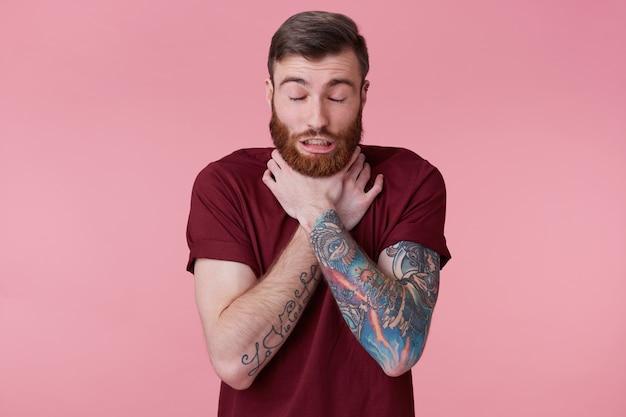 Zbliżenie na młody brodaty mężczyzna z tuszem dławiący się, cierpiący na silny ból gardła, odizolowany na różowym tle.