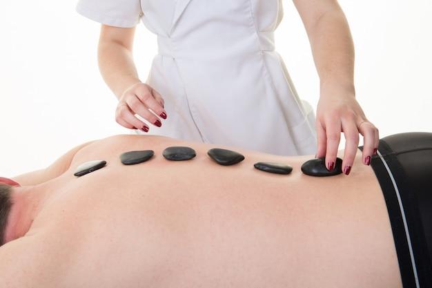 Zbliżenie na młody człowiek otrzymujący masaż gorącymi kamieniami z powrotem przez kobietę