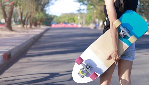 Zbliżenie na młodych kobiet ręka trzymać deskorolka, deskorolka surfingowa