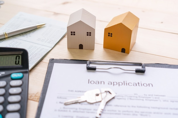 Zbliżenie na model domu, książkę bankową, papierkową robotę i kalkulator na drewnianym stole. nieruchomości, pożyczki, zbieranie pieniędzy i koncepcja inwestycji. leżał na płasko