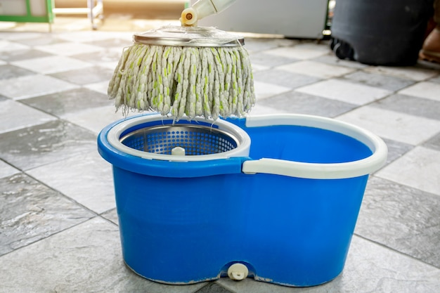 Zbliżenie na mopy i wiadro z produktami do czyszczenia podłóg.